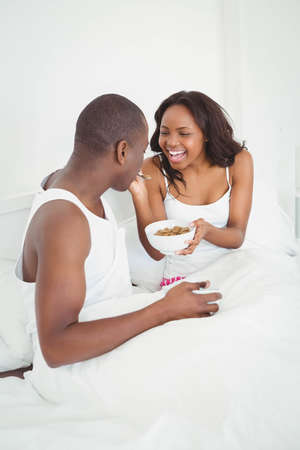 ethnic couple: Ethnic couple sharing a bowl of cereals in their bed