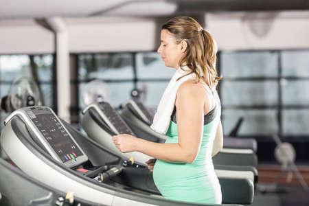 prenatal care: Smiling pregnant woman using treadmill at the leisure center