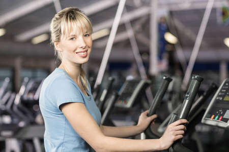 crosstrainer: Smiling woman on crosstrainer at the leisure center LANG_EVOIMAGES