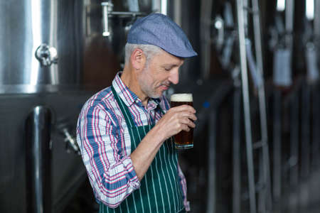 brewer: Happy brewer with his pint at the local brewery LANG_EVOIMAGES