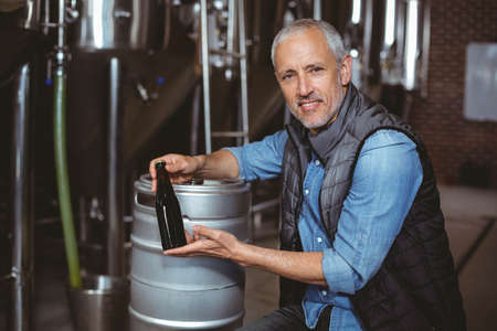 food products: Happy brewer showing his produce at the local brewery LANG_EVOIMAGES