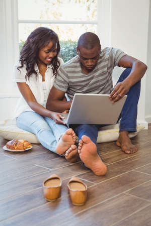 ethnic couple: Ethnic couple using laptop sitting in their new house LANG_EVOIMAGES