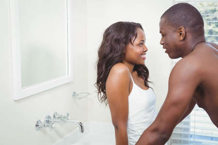 each: Ethnic couple looking at each other in the bathroom LANG_EVOIMAGES