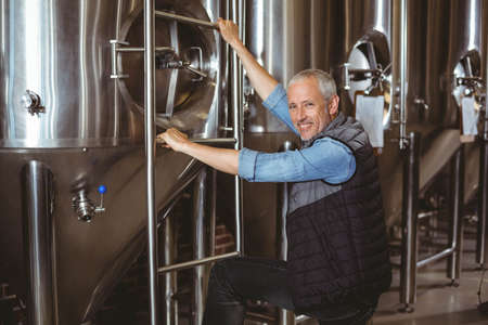 vats: Happy brewer checking large vats at the local brewery LANG_EVOIMAGES
