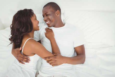 ethnic couple: Ethnic couple cuddling in bed LANG_EVOIMAGES