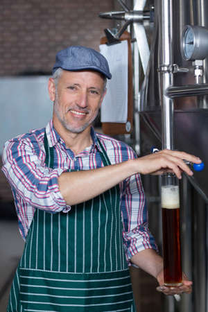 brewer: Happy brewer showing his produce at the local brewery LANG_EVOIMAGES