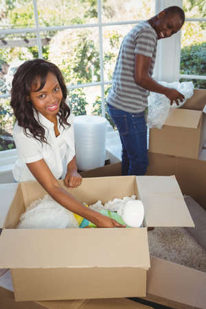 unwrapping: Ethnic couple unwrapping their stuff in boxes in their new house LANG_EVOIMAGES