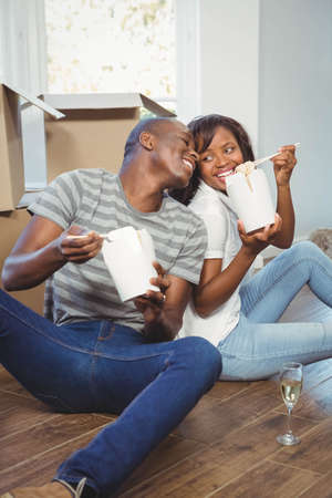 take away: Ethnic couple eating take away in their new house