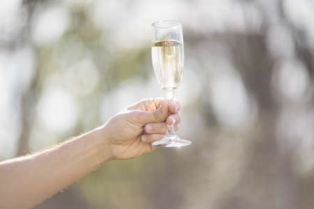 masculine: Masculine hand holding a glass of champagne in garden LANG_EVOIMAGES