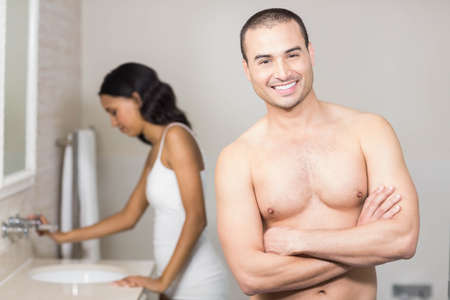 couple bathroom: Smiling couple looking at mirror in bathroom
