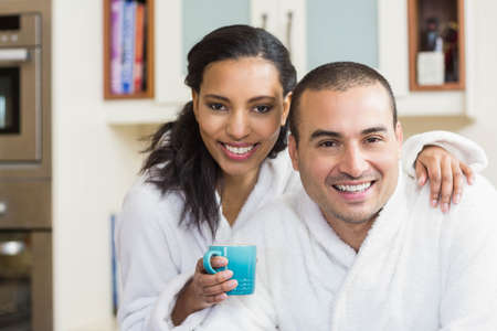 bath robe: Smiling couple drinking coffee in bath robe in the kitchen at home LANG_EVOIMAGES