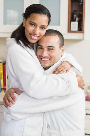 bath robe: Smiling couple embracing in bath robe in the kitchen at home LANG_EVOIMAGES