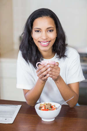 cereals holding hands: Smiling woman having breakfast in the kitchen at home LANG_EVOIMAGES