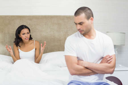 sad lady: Upset couple sitting on bed after having an argument at home LANG_EVOIMAGES