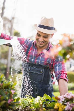 regar las plantas: El jardinero del hombre regar las plantas en el jard�n