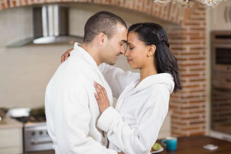 bath robe: Smiling couple hugging in bath robe in the kitchen at home