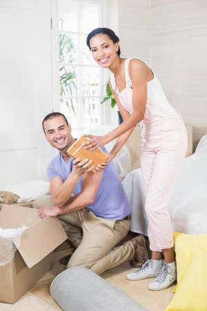 put away: Happy couple unpacking after move at home
