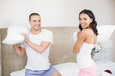pillow fight: Happy couple having a pillow fight in the bedroom at home