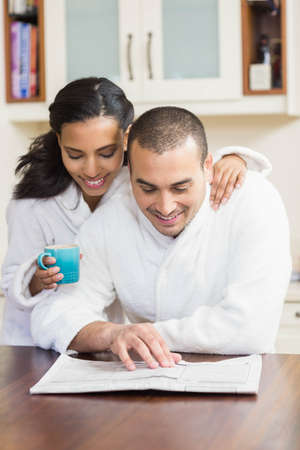 bath robe: Smiling couple reading newspaper in bath robe and drinking coffee in the kitchen