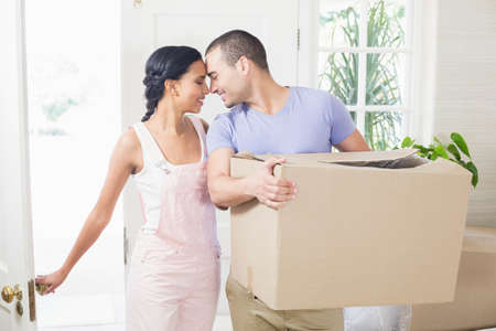 moving box: Happy couple entering in their new home with moving box at home