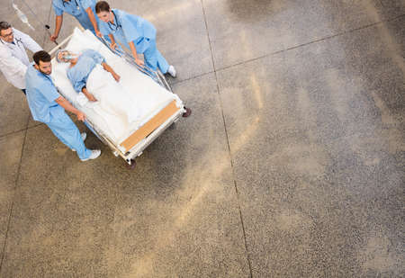 hospital trolley: Medical team pushing patient on trolley at the hospital
