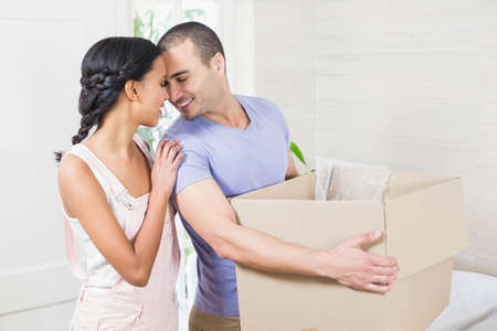moving box: Happy couple embracing with moving box at home LANG_EVOIMAGES