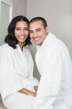 couple bathroom: Smiling couple wearing bathrobe in bathroom LANG_EVOIMAGES