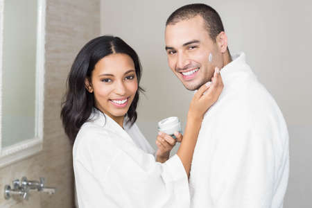 putting on: Smiling brunette putting on her husband cream in bathroom