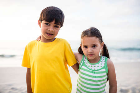 arms around: Cute siblings with arms around on the beach