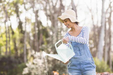 regar las plantas: Sonriendo morena plantas de riego en el jardín