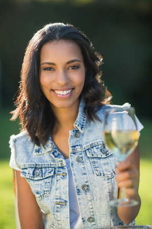 flute structure: Happy brunette drinking champagne in garden LANG_EVOIMAGES