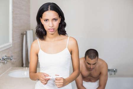 prueba de embarazo: pareja frustrada tener una prueba de embarazo positiva en el baño