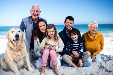 petting: Cute family petting a dog on the beach LANG_EVOIMAGES