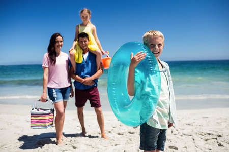beach buoy: Cute boy holding inflatable buoy on the beach with family in background LANG_EVOIMAGES