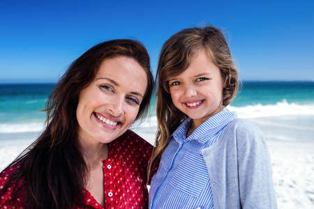 arms around: Mother and daughter smiling with arms around on the beach