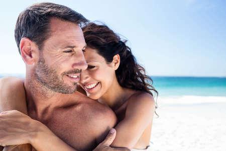 arms around: Cute couple cuddling with arms around on the beach