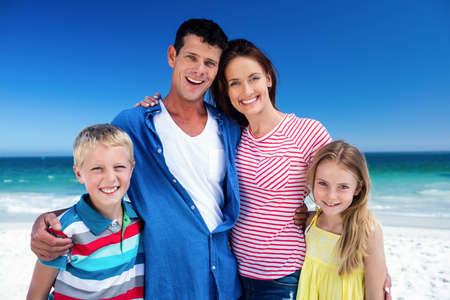 arms around: Cute family smiling with arms around on the beach LANG_EVOIMAGES