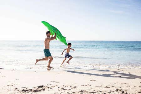 hombres corriendo: Padre e hijo que se ejecutan en la playa