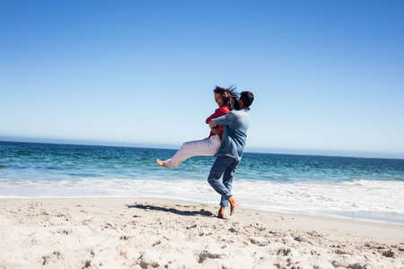 carrying girlfriend: Boyfriend carrying girlfriend and having fun on the beach LANG_EVOIMAGES