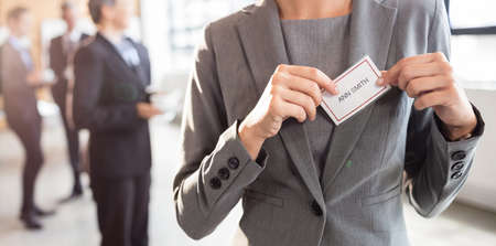 name badge: Businesswoman putting on name badge at the office