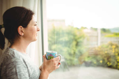 mid thirties: Portrait of woman with cup of coffee looking  through window LANG_EVOIMAGES