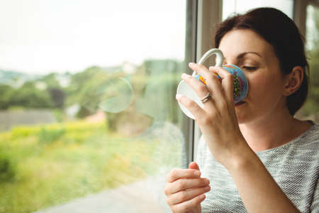mid thirties: Portrait of woman drinking coffee next to window LANG_EVOIMAGES