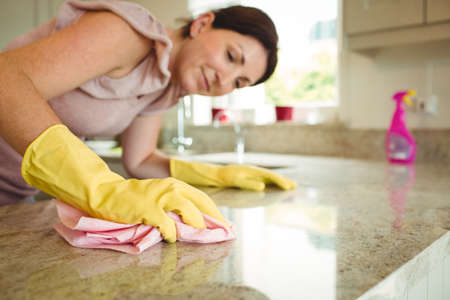 rubber gloves: Woman cleaning kitchen counter with cloth in rubber gloves