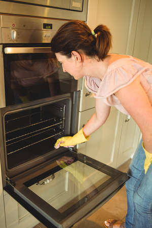 domicile: Woman cleaning the oven at home LANG_EVOIMAGES
