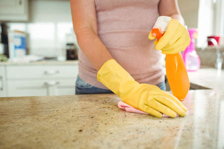domicile: Woman cleaning kitchen counter with cloth in rubber gloves