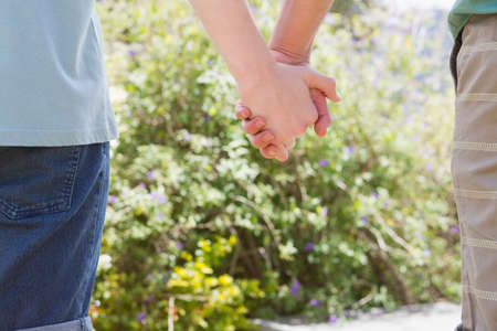 holding close: Close up of homosexual couple holding hands in the garden LANG_EVOIMAGES