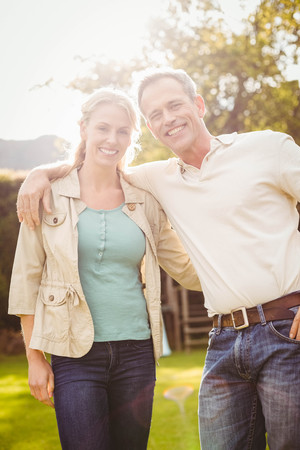 arms around: Cute couple with arms around outside Stock Photo