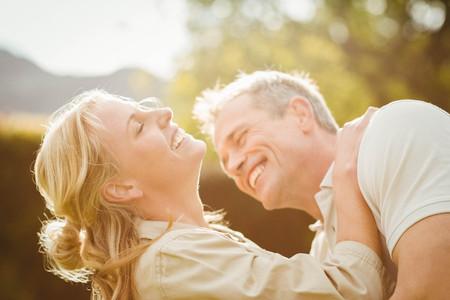 novios besandose: Esposo besando a la mujer en el cuello fuera