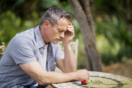 Depressed man touching his forehead sitting outside