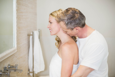husband kissing wife on the neck in the bathroom photo